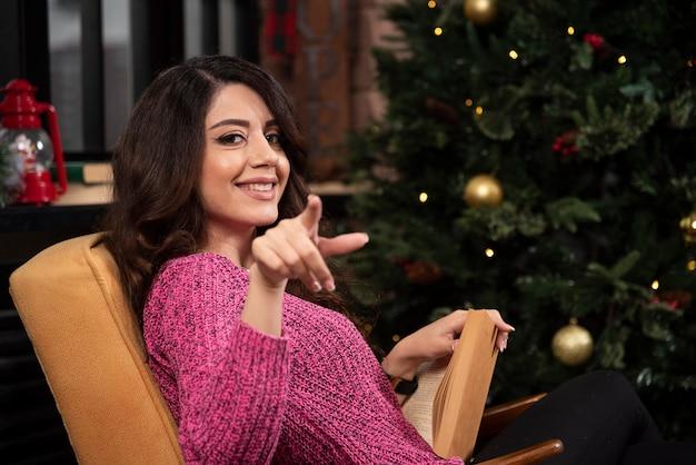 De glimlachende vinger van het jonge vrouwenpunt op camera. Gratis Foto