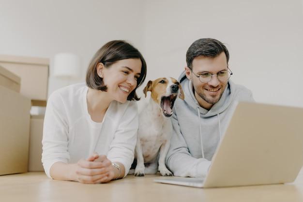 De glimlachende vrouw en de man werken aan moderne laptopcomputer, hondgeeuwen, kopen meubilair voor nieuw appartement, liggen op vloer in ruime lichte ruimte, hebben blije uitdrukkingen. housewarming en reparatie concept Premium Foto