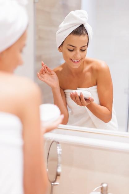 De glimlachende vrouw hydrateert de huid na het douchen Gratis Foto