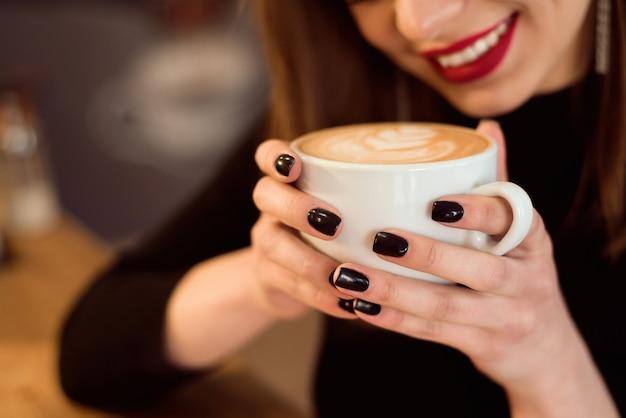 De glimlachende vrouw in een goede stemming geniet van kop van koffiezitting in een koffie. Premium Foto