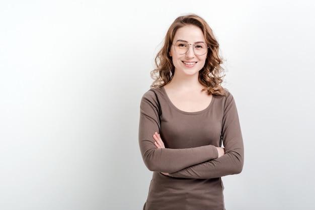 De glimlachende vrouw in glazen bevindt zich met gekruiste wapens Premium Foto