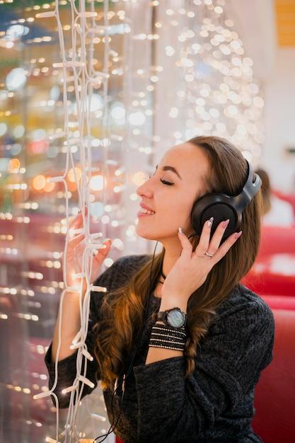 De glimlachende vrouw met ogen sloot holdingshoofdtelefoons op hoofd wat betreft kerstmislichten Gratis Foto