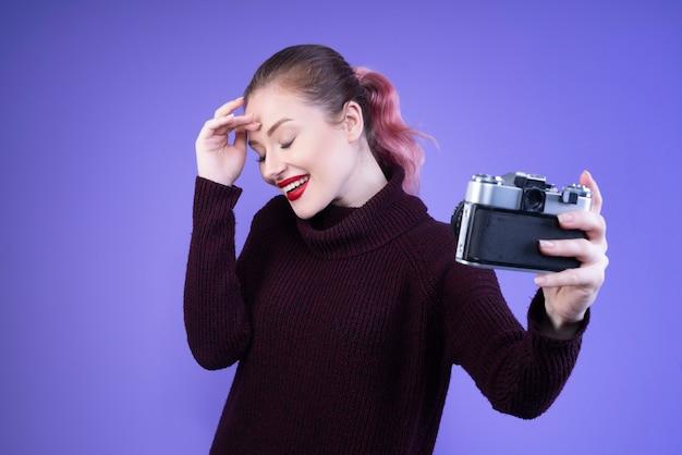 De glimlachende vrouw met rode lippen probeert selfie met een camera te nemen Gratis Foto