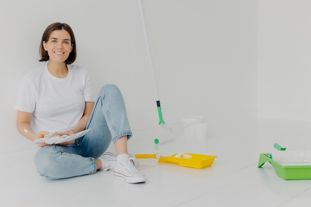 De glimlachende vrouwenontwerper kiest beste kleur voor flat Premium Foto