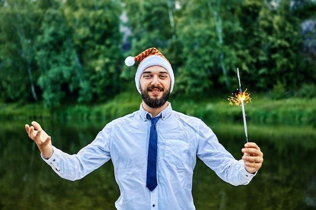 De glimlachende zakenman van houng, met een kerstman-hoed, houdt een brandend sterretje in zijn hand, staande tegen de achtergrond van groene bomen en rivier in het wild. Premium Foto