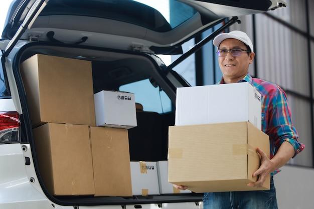 De goede doos van de aziatische mensenlevering aan klant in fabriek en handtekening op tabletglimlach en de goede dienst, logistiek het winkelen online concept Premium Foto