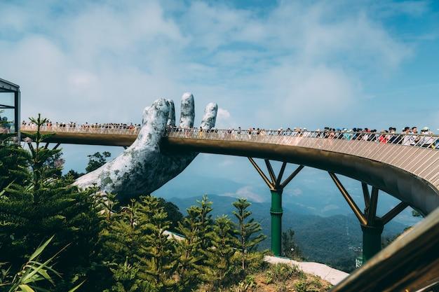 De gouden brug wordt opgeheven door twee gigantische handen in het toeristenoord op ba na hill in danang, vietnam. ba na hill bergresort is een favoriete bestemming voor toeristen van centraal vietnam Premium Foto