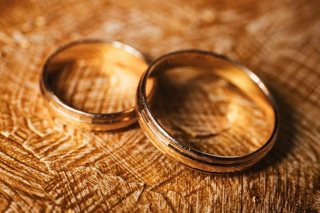 De gouden ringen van het huwelijk liggen op achtergrond die met slagen van olie bruin-gouden verf wordt behandeld. Premium Foto