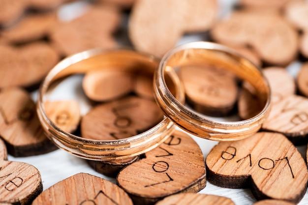 De gouden ringen van het paarhuwelijk op houten harten met geschroeide inschrijvingsliefde op witte achtergrond. Premium Foto