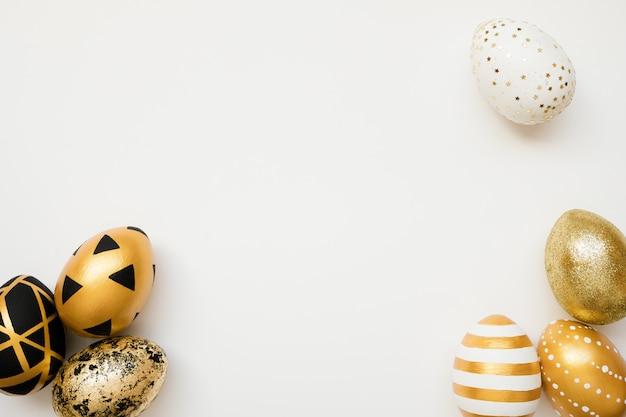 De gouden verfraaide eieren van pasen die op witte achtergrond worden geïsoleerd Premium Foto
