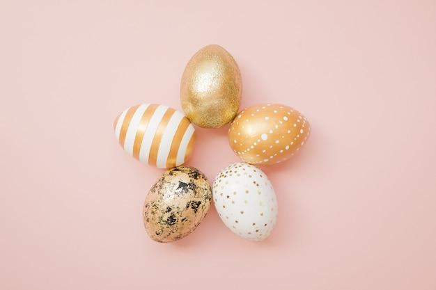 De gouden verfraaide eieren van pasen op pastelkleur roze achtergrond Premium Foto
