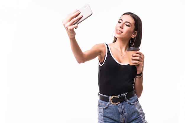 De grappige dame met donkerbruin haar maakt selfie op haar telefoon geïsoleerd Gratis Foto