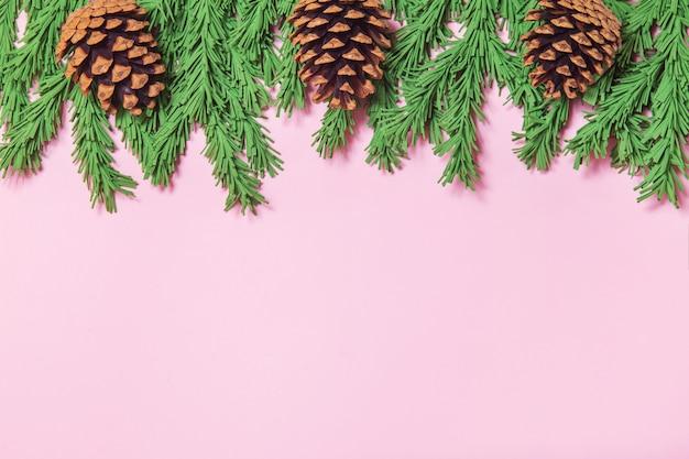 De groene de takgrens van de schuimkerstboom met kegels op de roze vlakte als achtergrond lag Premium Foto