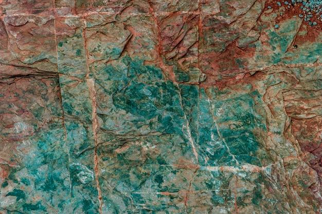 De groene en rode geologie van de rots kleurrijke textuur voor textuur en achtergrondontwerp. Premium Foto