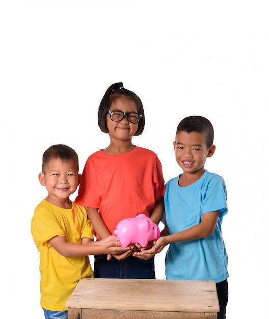De groep aziatische kinderen heeft pret met spaarvarken op witte achtergrond wordt geïsoleerd die Premium Foto