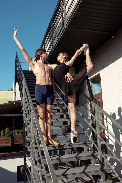 De groep moderne balletdansers die op de treden bij de stad presteren Gratis Foto