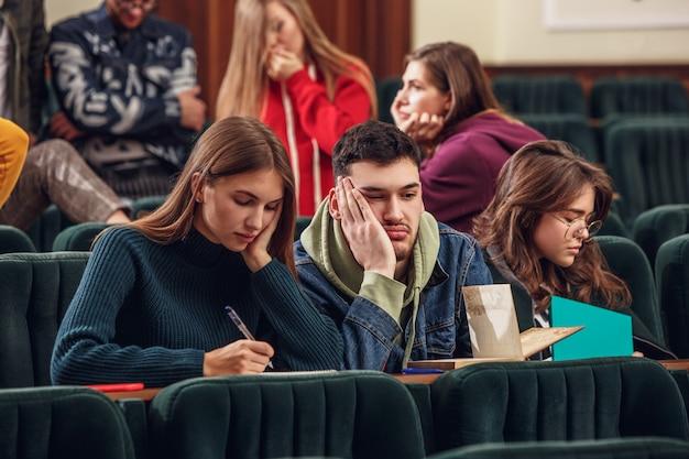 De groep van vrolijke gelukkig studenten zitten in een collegezaal voor de les Gratis Foto