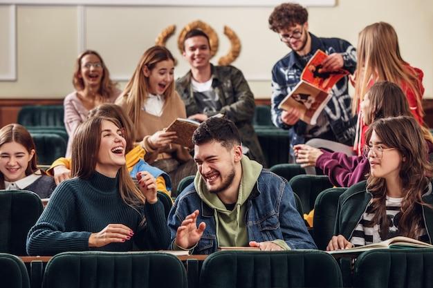 De groep vrolijke gelukkige studenten die vóór les in een collegezaal zitten Gratis Foto