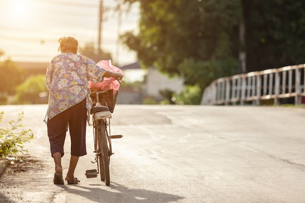 De grootmoeder die met oude fiets op de straat loopt Premium Foto