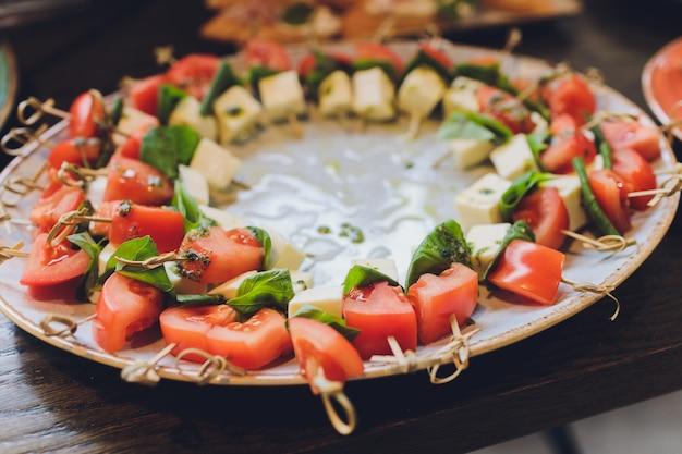 De grote plaat van de close-up met het dienen de peterselie en de salami van de snack canapes gebraden brood. Premium Foto