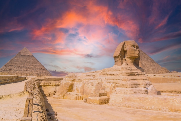De grote sfinx van gizeh en op de achtergrond de piramides van gizeh bij zonsondergang, het oudste grafmonument ter wereld. in de stad caïro, egypte Premium Foto
