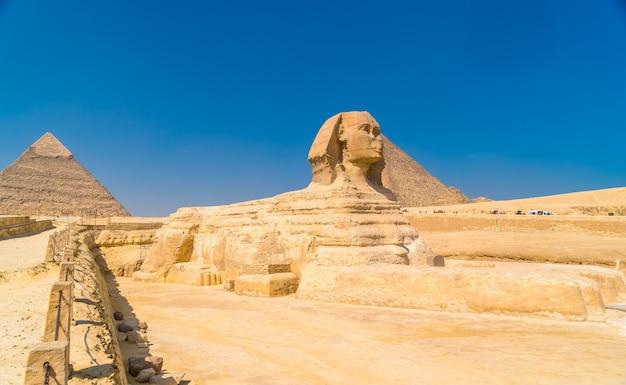 De grote sfinx van gizeh en op de achtergrond de piramides van gizeh, het oudste grafmonument ter wereld. in de stad caïro, egypte Premium Foto