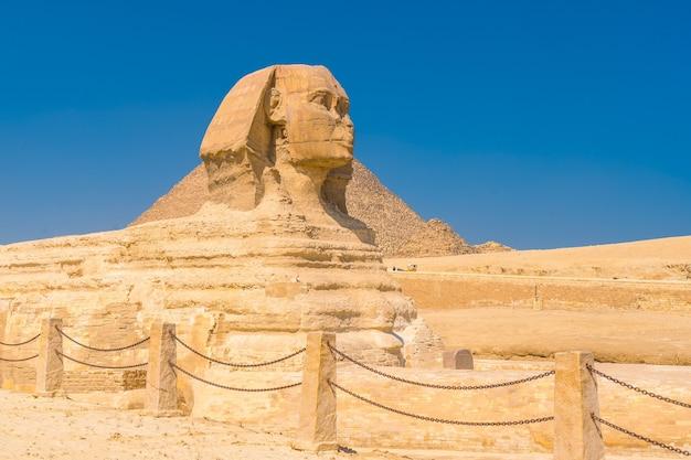 De grote sfinx van gizeh en op de achtergrond de piramides van gizeh op een zomermiddag, het oudste grafmonument ter wereld. in de stad caïro, egypte Premium Foto