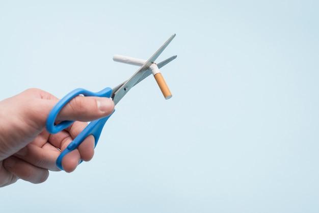 De hand bemiddelende sigaret van de persoon met schaar over blauwe achtergrond Gratis Foto