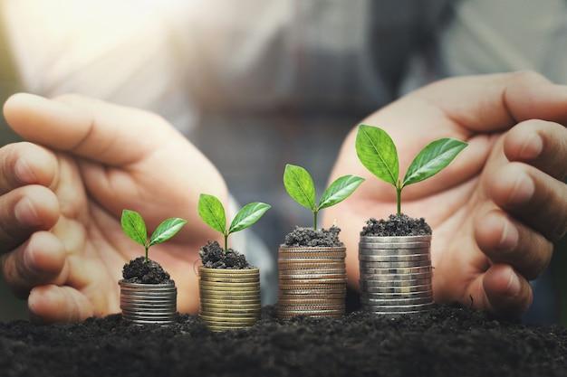 De hand beschermt geldstapel met installatie het groeien op muntstukken. conceptfinanciën Premium Foto