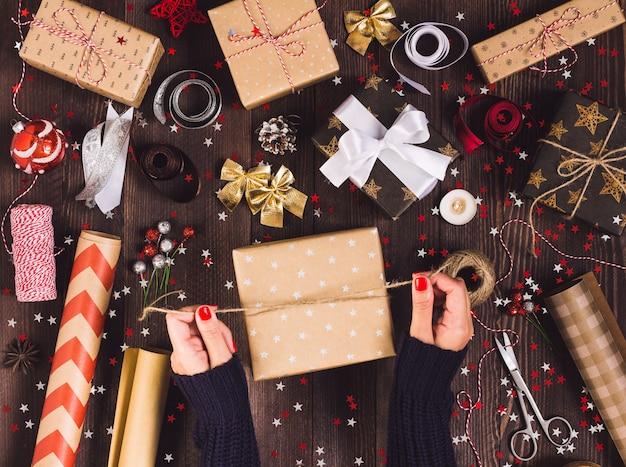 De hand bindende boog van de vrouw met streng voor het verpakken van de doos van de kerstmisgift Gratis Foto