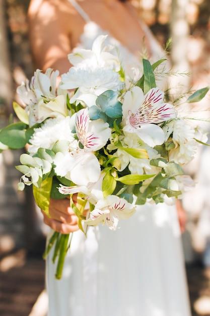 De hand die van de bruid peruviaanse lelie en gerbera houdt bloeit boeket in hand Gratis Foto