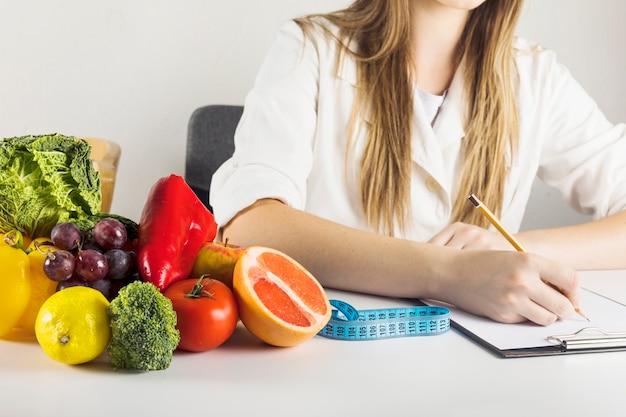 De hand die van de diëtist op klembord met gezond voedsel op bureau schrijft Gratis Foto