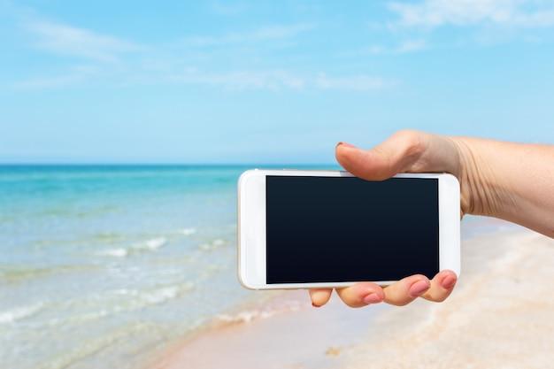 De hand die van de mooie vrouw slimme telefoon met behulp van bij strand Premium Foto