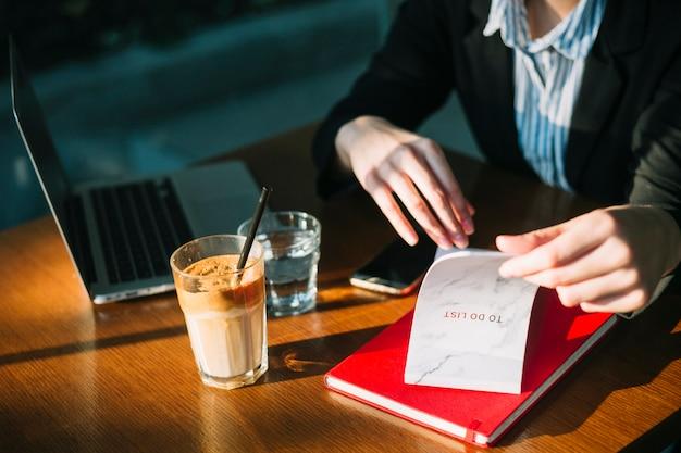 De hand die van de onderneemster de lijst in restaurant controleert te doen Gratis Foto