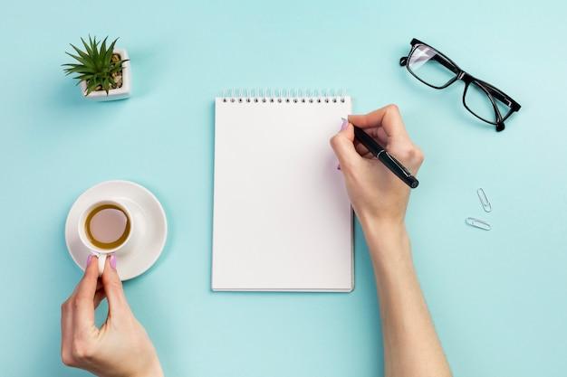 De hand die van de onderneemster op blocnote met pen schrijft en koffiekop over het bureau houdt Gratis Foto