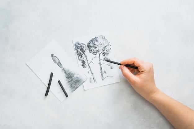De hand die van de persoon mooie tekening met houtskoolstok schetsen op witte oppervlakte Gratis Foto