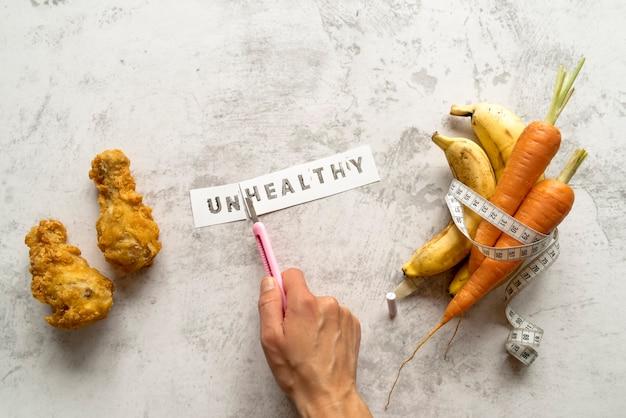 De hand die van de persoon ongezond woord snijdt dichtbij gebraden die kip met banaan en wortelen in het meten van band worden gerold Gratis Foto
