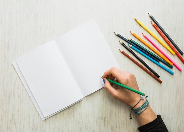 De hand die van de persoon op leeg wit boek schrijft dat kleurenpotlood gebruikt Gratis Foto