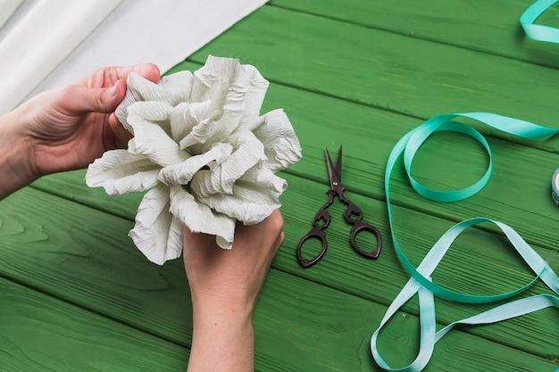 De hand die van de persoon valse crêpepapierbloem op groene geweven achtergrond houdt Gratis Foto