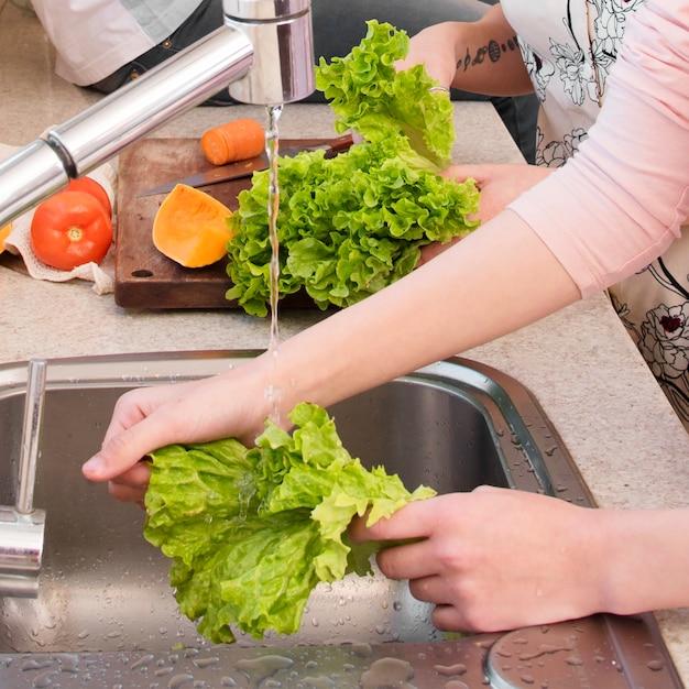 De hand die van de vrouw de sla in de keukengootsteen wast Gratis Foto