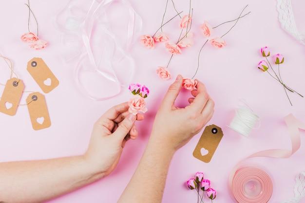 De hand die van de vrouw de valse bloemen met lint en markering op roze achtergrond schikken Gratis Foto