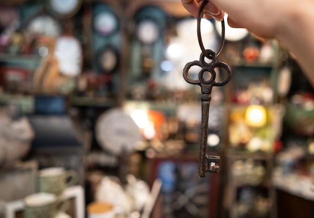 De hand die van de vrouw een antieke sleutel houdt Gratis Foto