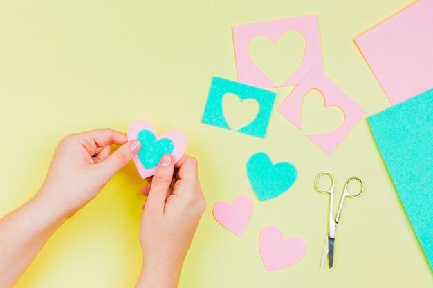 De hand die van de vrouw hartvorm met blauw en roze document op gele achtergrond maakt Gratis Foto