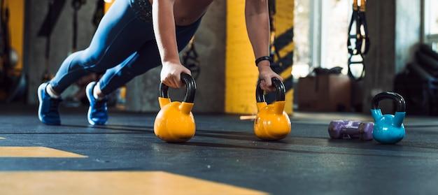 De hand die van de vrouw opdrukoefeningen op ketelbal doet in gymnastiek Gratis Foto