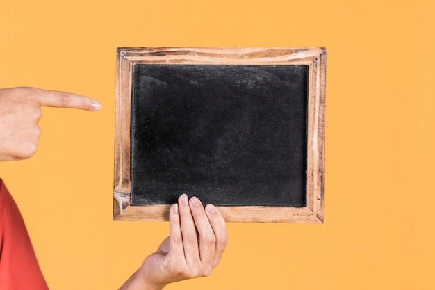 De hand die van de vrouw over lege lei op gele achtergrond richt Gratis Foto
