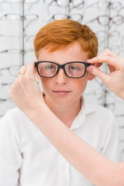 De hand die van de vrouw schouwspel draagt aan jongen in opticawinkel Gratis Foto