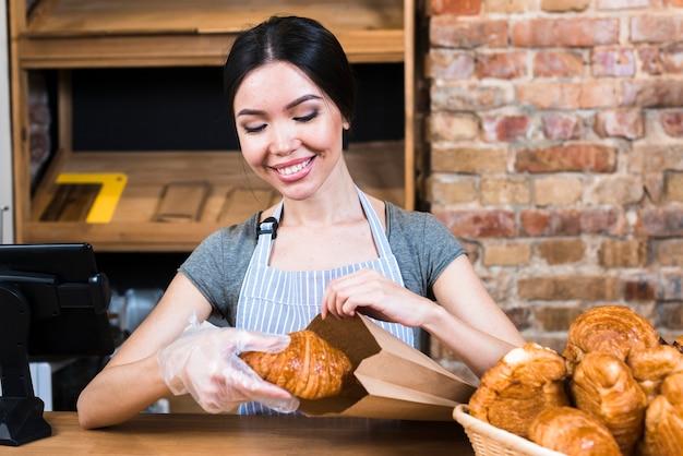 De hand die van de vrouwelijke bakker handschoen draagt die gebakken croissant in document zak verpakt Gratis Foto
