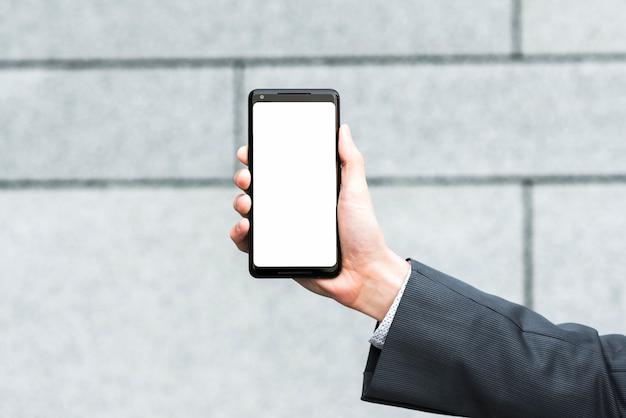 De hand die van de zakenman het lege mobiele scherm tegen vage achtergrond toont Gratis Foto