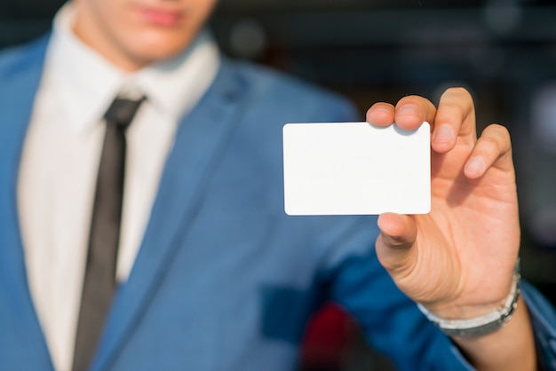 De hand die van de zakenman lege witte kaart toont Gratis Foto