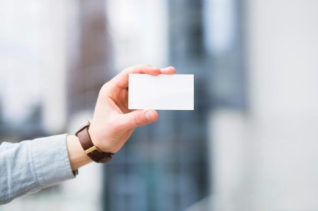De hand die van de zakenman wit leeg visitekaartje toont Gratis Foto